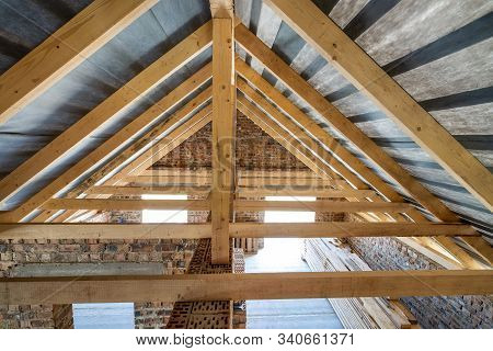 Attic of a building under construction with wooden beams of a roof structure and brick walls. stock photo
