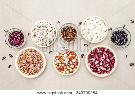 Assortment of beans on a stone background. Crimson cranberry, red, painted pony, black turtle, brown, black-eyed, Jacob's Cattle (heirloom) and lima stock photo