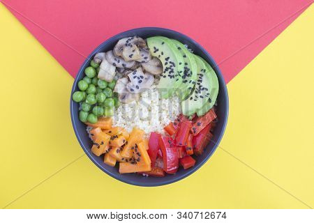 Vegan poke bowl with couscous  and vegetables in the black bowl in the center of the bicolor background. Top view. Copy space. Closeup. stock photo