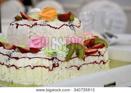 Cream birthday cake with roses. Luxurious anniversary sweet symbol. stock photo