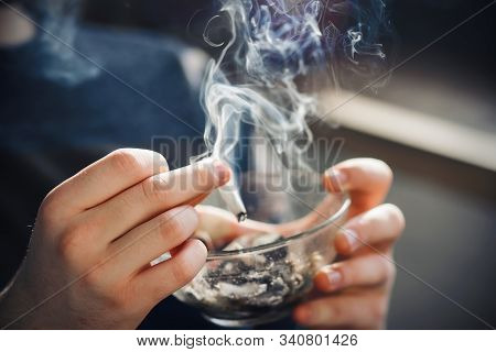 A man holds a glass ashtray filled with cigarette butts and flicks ash from a cigarette into it, which emits thick smoke, illuminated by sunlight. stock photo