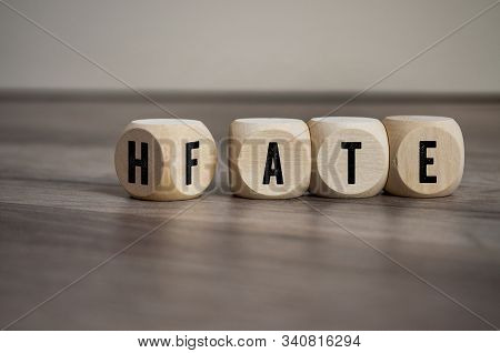 Cubes and dice with the opposite of hate and fate on wooden background stock photo