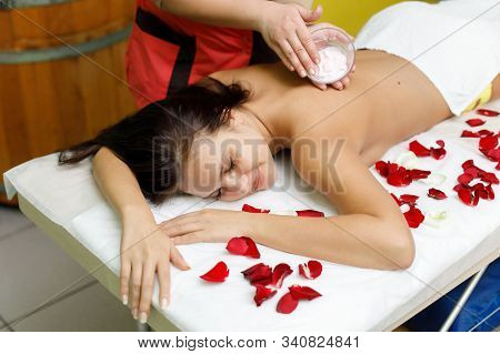 Masseur applying cream to woman's back. Rose petals. Massage in spa salon stock photo