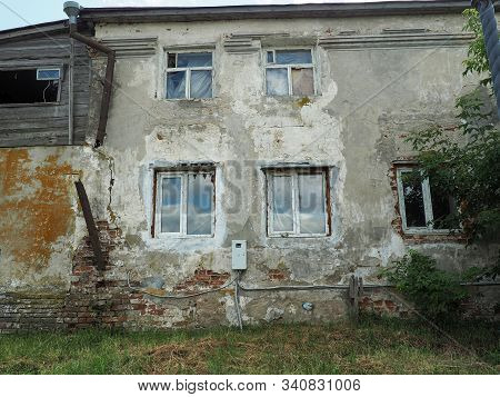 Old four-storey abandoned dilapidated house. Very old residential building. Apartment building. stock photo