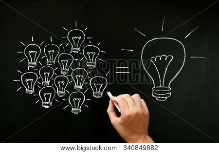 Hand drawing with chalk on blackboard light bulbs concept illustrating how a business team is working together creating a great idea. Many small ideas add up to a big one. stock photo