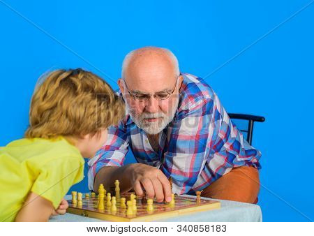Little boy playing chess with grandfather at home. Grandfather and grandson playing chess. Grandpa and grandson playing chess spending free time together. Grandpa teaching his grandson to play chess. stock photo