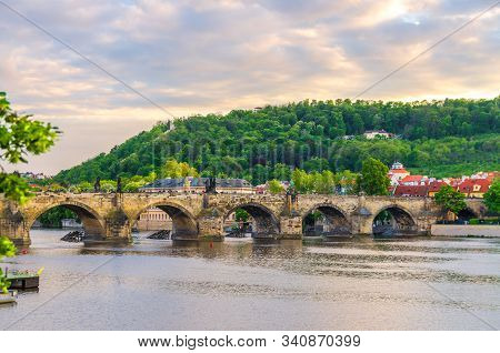 Charles Bridge Karluv Most with alley of dramatic baroque statues over Vltava river in Old Town of Prague historical center, garden on slope of Petrin Hill background, Czech Republic, Bohemia, Europe stock photo