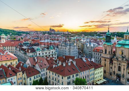 Top aerial panoramic view of Prague Old Town historical city centre with red tiled roof buildings and Prague Castle, St. Vitus Cathedral in Hradcany district in evening sunset, Bohemia, Czech Republic stock photo