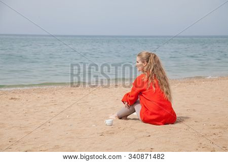 Beautiful blonde woman drinks hot drink on the beach by the sea stock photo