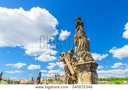 Madonna and Saint Bernard statue on Charles Bridge Karluv Most over Vltava river with Prague Castle, St. Vitus Cathedral in Hradcany district, blue sky white clouds background, Bohemia, Czech Republic stock photo