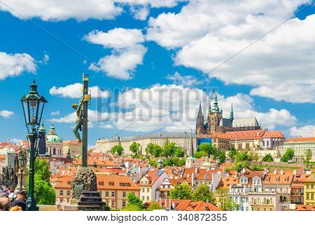 Crucifix and Calvary statue on Charles Bridge Karluv Most over Vltava river with Prague Castle, St. Vitus Cathedral in Hradcany district, blue sky white clouds background, Bohemia, Czech Republic stock photo