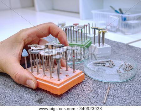 Dental medical tools, dentist equipment. Stomatological drills, milling cutters for  dental burs  on light blue dentist table. stock photo