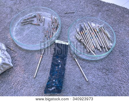 Dentist tools for grinding and shaping a metal dental prosthesis. Set of dental burs and dental articulator in a lab stock photo