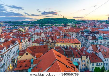 Top aerial panoramic view of Prague Old Town (Stare Mesto) historical city centre with red tiled roof buildings and Petrin hill garden in evening sunset, Bohemia, Czech Republic stock photo
