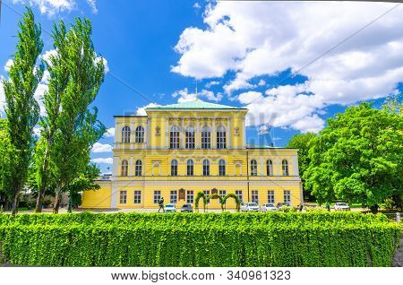 Yellow Zofin palace Neo-Renaissance building, green trees and bushes, Zofin island on Vltava river in Old Town of Prague historical center, blue sky white clouds background, Bohemia, Czech Republic stock photo