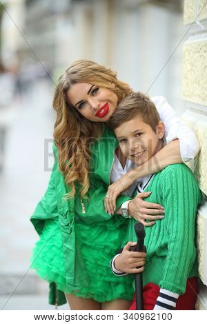 Young beautiful mother blonde hugs adult boy son. stock photo