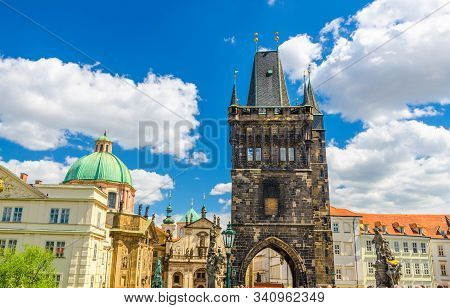 Prague Old Town Bridge Tower on Charles Bridge Karluv Most over Vltava river, St. Salvator Church in Klementinum in historical city centre, blue sky white clouds background, Bohemia, Czech Republic stock photo