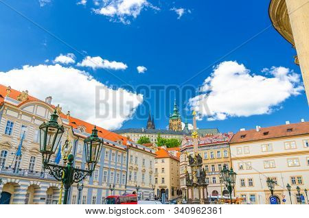 Academy of Performing Arts, Column of the Holy Trinity and street lights on square in Mala Strana district, St. Vitus Cathedral spire, blue sky white clouds background, Bohemia, Czech Republic stock photo