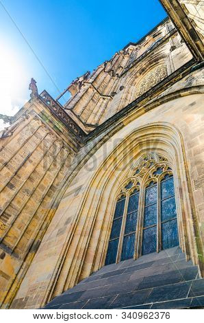 View from below of window of South Tower - exterior of St. Vitus Cathedral in Prague Castle Hradcany Lesser Town Mala Strana district, blue sky background, Bohemia, Czech Republic stock photo