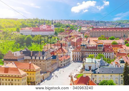 Top aerial view of Prague Castle district with Hradcany Square, green gardens on slope of hill, Schwarzenbersky and Toskansky palace, blue sky white clouds background, Bohemia, Czech Republic stock photo