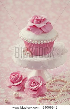 Cupcake with rose flower on a stand stock photo