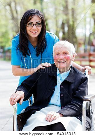 Kind doctor nurse outdoors taking care of an ill elderly woman in wheelchair. stock photo