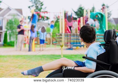 Disabled little boy in wheelchair sadly watching children play on playground stock photo