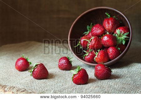 Strawberry natural healthy nutrition organic food in rustic clay dish on vintage kitchen background.