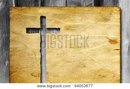 Vintage old grungy paper banner with a Christian religious cross over ancient wood background for re