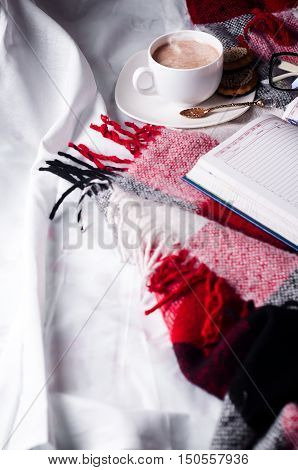 Cup of cocoa staying on open book and glases on the bed with blanket Good morning. stock photo
