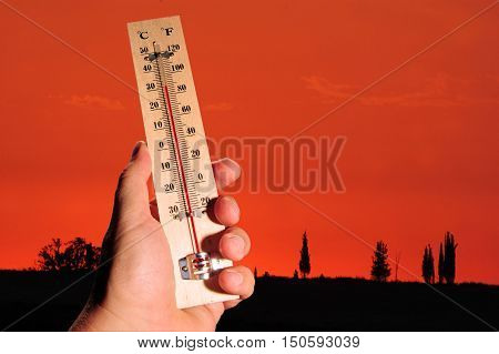 A hand and temperature scale over a red sky shows high temperatures during a heat wave.