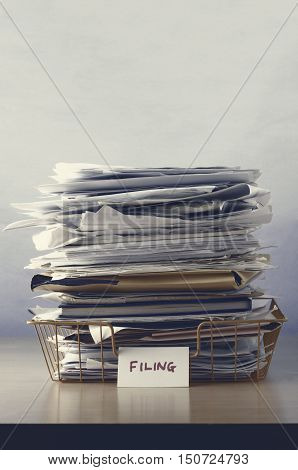 A filing tray with label piled up with papers and folders undersaturated in drab hues for dreary dystopianfeel. stock photo