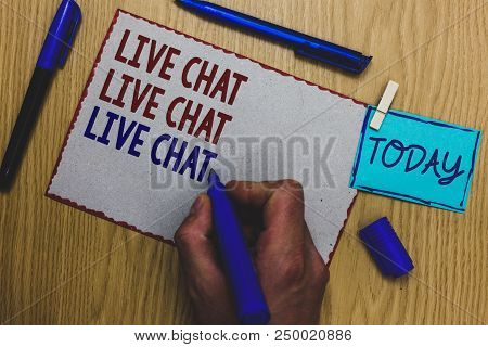 Conceptual hand writing showing Live Chat Live Chat Live Chat. Business photo text talking with people friends relatives online Man holding marker paper clothespin express ideas wooden table stock photo