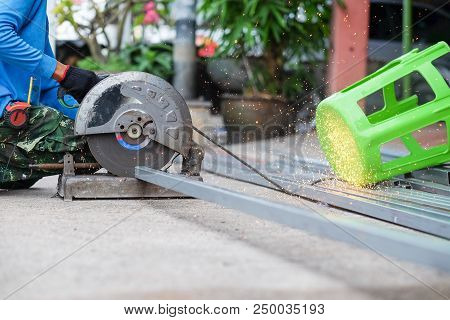 The man working on cutting a metal and steel with compound mitre saw stock photo