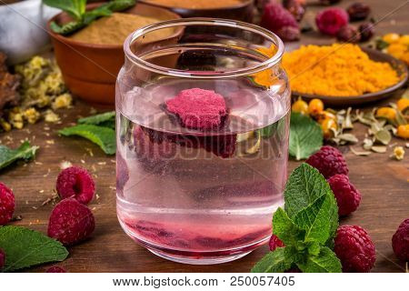 Raspberry extract stir in the water shot close-up stock photo