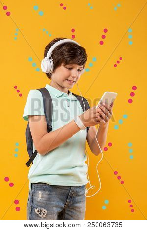 Watching videos. Progressive kid standing with a backpack and wearing big modern headphones while watching videos on the screen of his smartphone stock photo