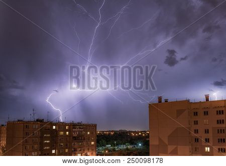night city view under thunderstorm with strike of lightning. Powerful thunderbolt during thunderstorm in the city. Cloud to ground electric lightning behind the city. stock photo