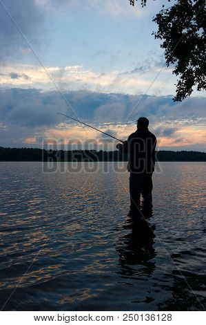 Silhouette of angler catching the fish during cloudy sunrise stock photo