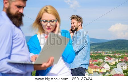 Colleagues laptop work outdoor sunny day, sky background. Outdoor workspace concept. Friends enjoy fresh air and keep working. Colleagues with laptop discussing plan. Fresh air helps to refresh mind. stock photo