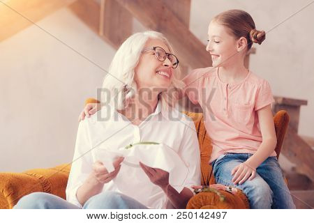 Love you to the moon and back. Beautiful elderly lady and her adorable grandchild smiling cheerfully while both sitting in an armchair and hugging during an embroidering session. stock photo