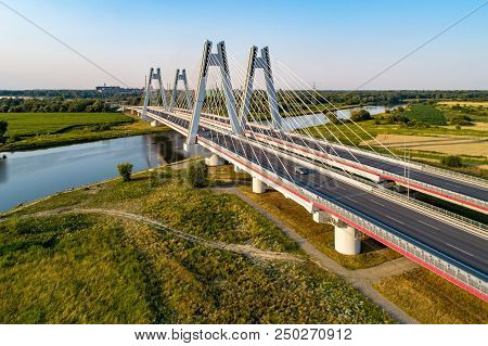 New modern double cable-stayed bridge over Vistula River in Krakow, Poland. Part of the ring motorway around Krakow under construction. Aerial view at sunset. Sedzimir Steel mill in the background. stock photo