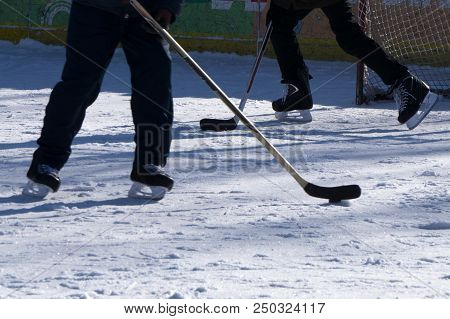 A boy ice hockey amateur player with a stick and a puck on ice. Feet in hockey skates and a stick and a puck and ica background. Half of amateur hockey player's figure, ready to hit the puck on ice stock photo