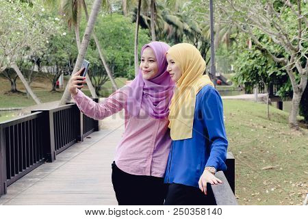 Happy attractive muslimah having fun, spend time together and selfie at the city park stock photo