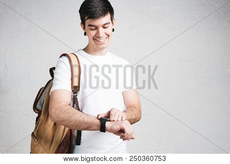 Smiling young man wearing white t-shirt and packpack, studio portrait stock photo