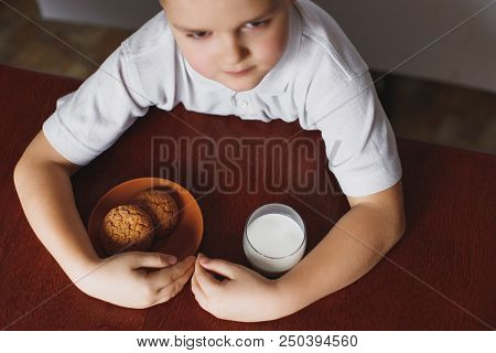 A little boy eats oatmeal cookies and drinks with home-made milk. Healthy breakfast prepared by my mother. The schoolboy is having breakfast. stock photo