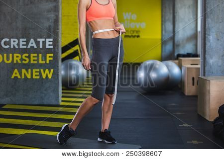 Slim woman is standing in gym and assessing training progress. She is using centimeter band for measuring belly volume. Improving body shape by regular exercising concept stock photo