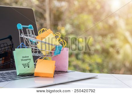 Colorful paper bags are in trolley on laptop keyboard. Consumers can buy products directly  from a seller over internet using web browser. Ideas about online shopping and e-commerce. stock photo
