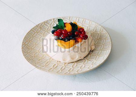 Tasty Pavlova dessert on porcelain plate with white meringue, cream and fruit. Traditional Australian sweet food. stock photo