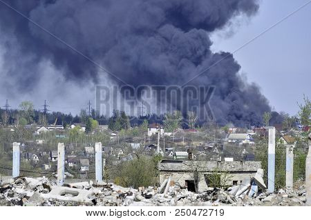 A pile of concrete rubble with protruding rebar on the background of thick black smoke in the blue sky. Background. The concept of the consequences of human activities. stock photo