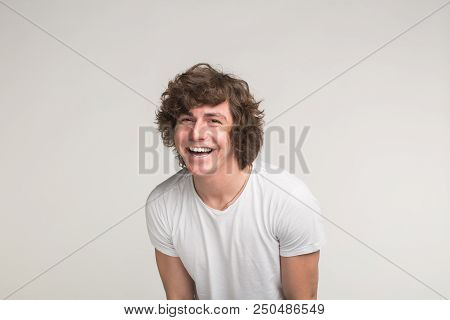 Handsome young man posing and laughing in white t-shirt in motion stock photo